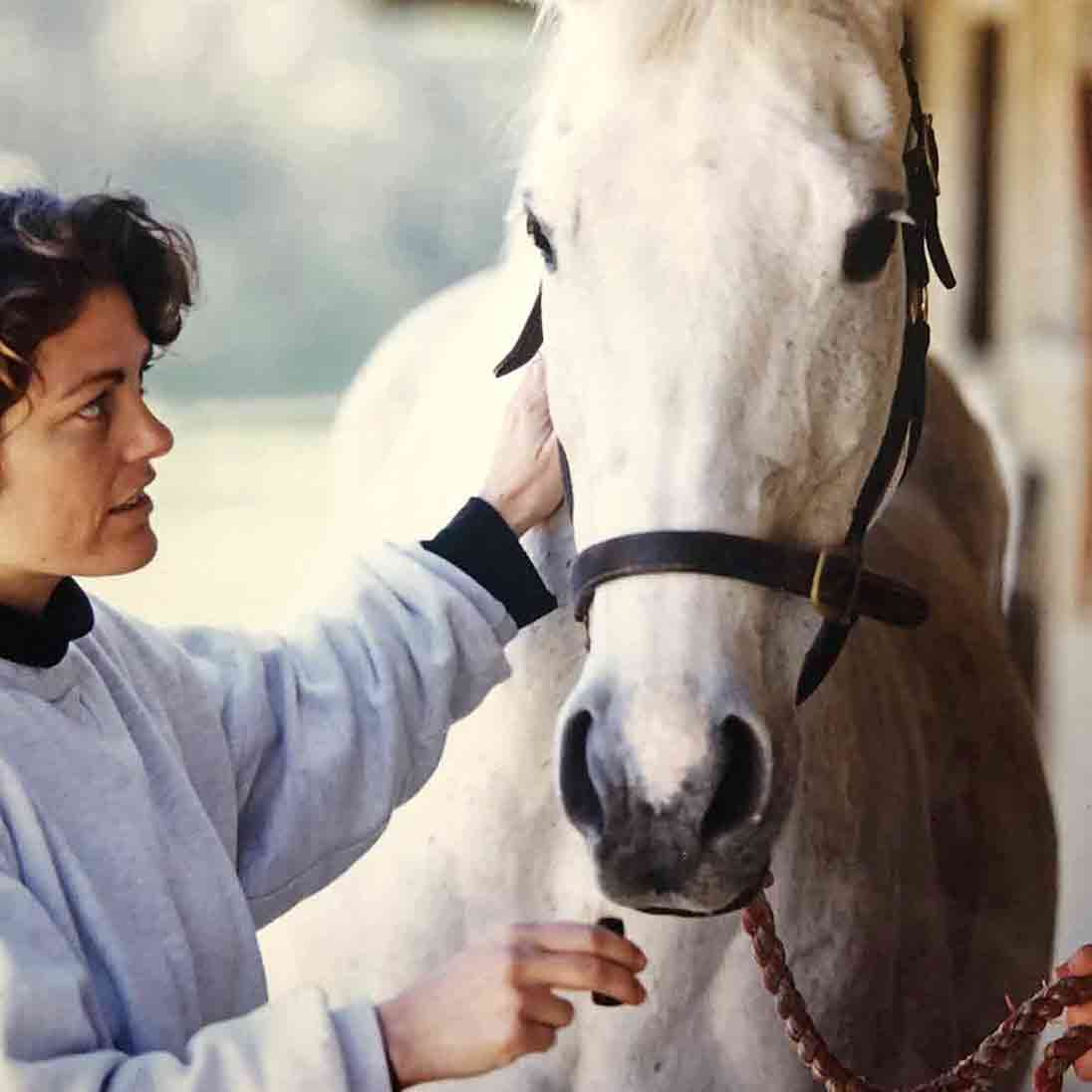 Caroline Ingraham Offering Essential Oils To A White Horse